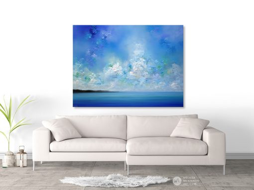 Seascape art print on canvas of blue ocean sea and cloudy sky by Melissa McKinnon hanging above sofa title Horizon Blue