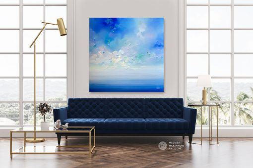 Abstract sky art print on canvas of cloudy sky over blue ocean seascape by artist Melissa McKinnon hanging over modern sofa title New Horizons