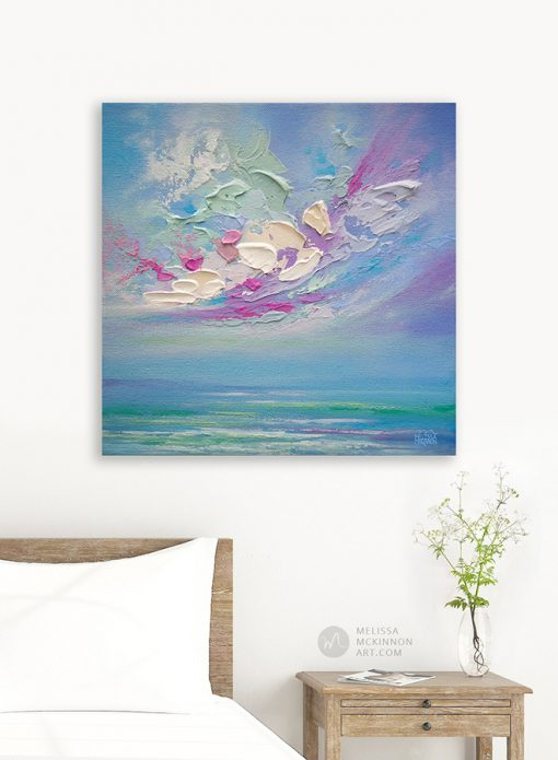 Affordable giclee art print on canvas of abstract seascape and sunset sky clouds by Melissa McKinnon hanging in a modern bedroom title Swept Away