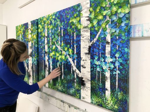 Contemporary Canadian artist Melissa McKinnon painting aspen birch trees with a palette knife and acrylic paint in her studio in Calgary, Alberta