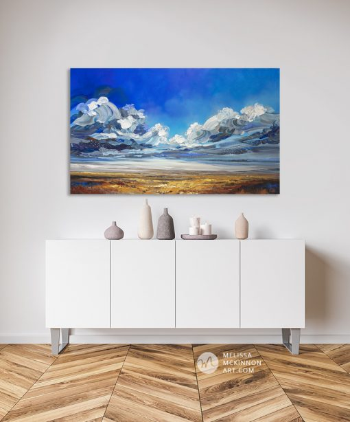 """Dramatic landscape painting of cloudy stormy sky over prairie field by contemporary Canadian Artist Melissa McKinnon displayed in modern home interior """"Can't Tame the Wild"""""""